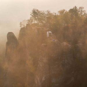 Die Bastei in der Sächsischen Schweiz umhüllt von Nebel bei orangefarbenem Morgenlicht
