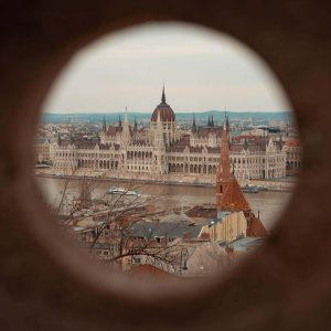 Das Parlamentsgebäude in Budapest wird eingerahmt durch ein Loch in der Mauer der Fischer Bastei
