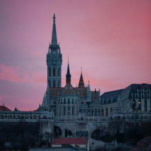 Die Fischer Bastei in Budapest vor pink-farbenem Himmel bei Sonnenuntergang