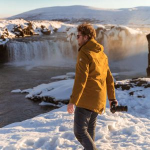 Unser Reisefotograf Dorian geht mit seiner Kamera zum Wasserfall Godafoss