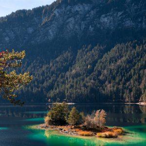 Ein Insel im Eibsee in Bayern wird von der Sonne gelb angeleuchtet in grün-blauem Wasser