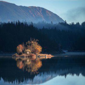 Ein Insel im Eibsee in Bayern wird kurz nach Sonnenaufgang gelb angeleuchtet im blauen Wasser