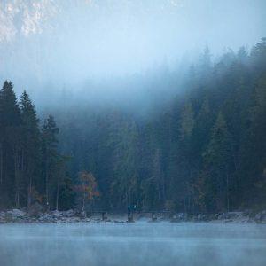 Der Eibsee früh am Morgen ist bedeckt von Nebel während in der Ferne einige Leute über eine Brücke laufen