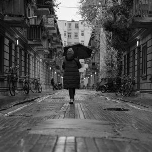 Ein Mädchen mit Regenschirm steht in einer Gasse in Hamburg