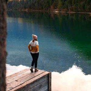 Hanna steht auf einem Bootsanleger am Plansee mit Bergen im Hintergrund