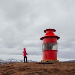 Hanna mit roter Regenjacke neben einem kleinen roten Leuchtturm in Stykkishólmur
