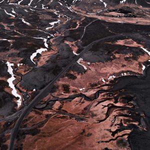 Einen Drohnen Luftaufnahme von rot-schwarzer Landschaft in Island