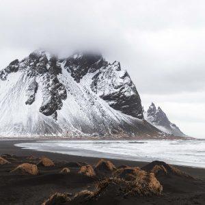 Schwarze Berge mit Schnee bedeckt davor schwarzer Sandstrand bei Stokksnes, Island