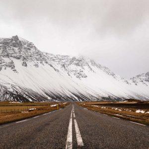 Eine lange Straße in Island, die auf weiße verschneite Berge zuführt