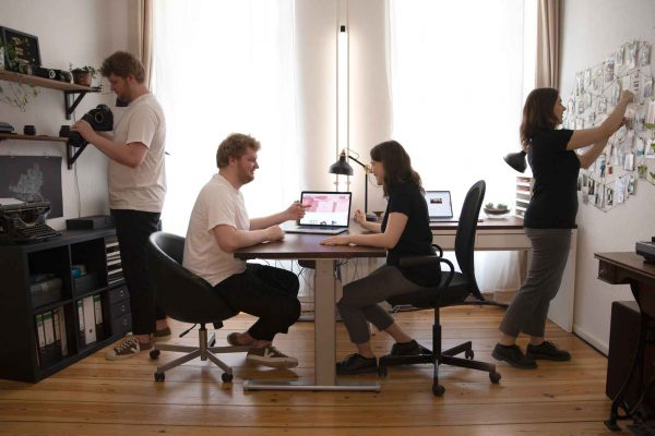 Hanna und Dorian sitzen am Schreibtisch und arbeiten gemeinsam an einem Laptop. Gleichzeit steht eine 2. Hanna daneben an einem Visionboard und ein zweiter Dorian nimmt eine Kamera aus dem Regal.