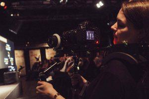 Hanna filmt das Geschehen auf der Bühne mit einem Schulterrig und blickt auf das Display der Kamera