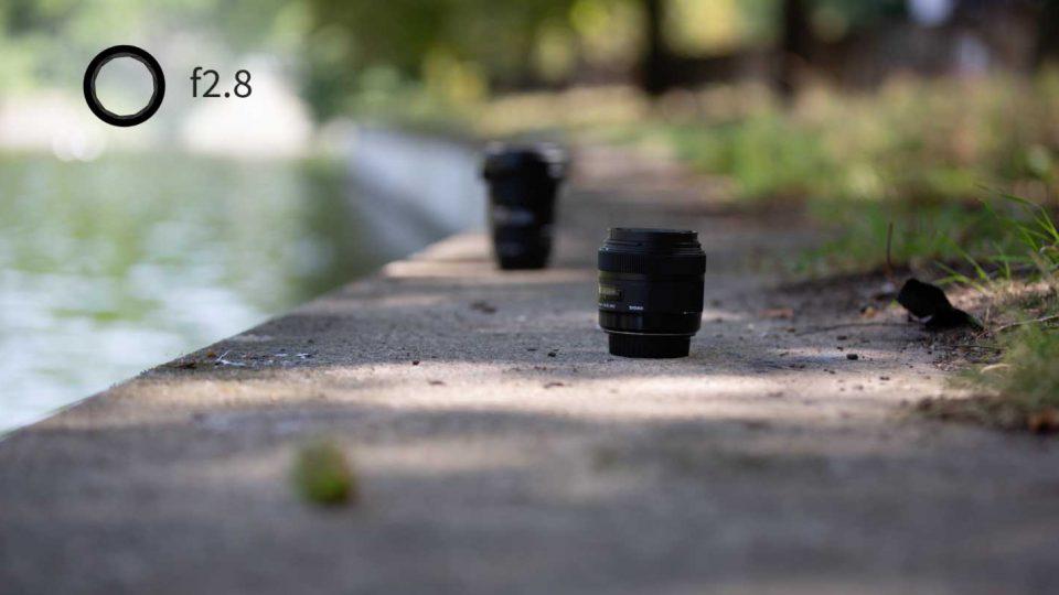 Ein Foto von drei Objekten, bei dem nur einer scharf ist. Eine Grafik zeigt eine Blende von 2.8, was die geringe Schärfentiefe im Bild erklärt