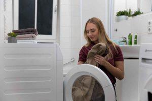 Vanessa von Finnto steckt einen Bezug des Hundebetts in die Waschmaschine.