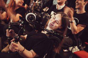 Unsere Filmemacherin Hanna filmt das GWA Event mit einem Schulterrig und lächelt zufrieden