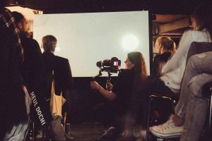 Hanna sitzt im Gang zwischen dem Publikum und filmt das GWA Event mit einem Schulterrig.