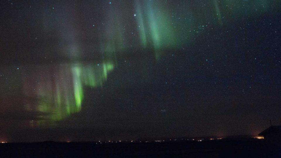 Ein Bild aus Island von grünen Nordlichtern und Sternen als Beispiel für die Regulation des ISO bei Nachtfotografien