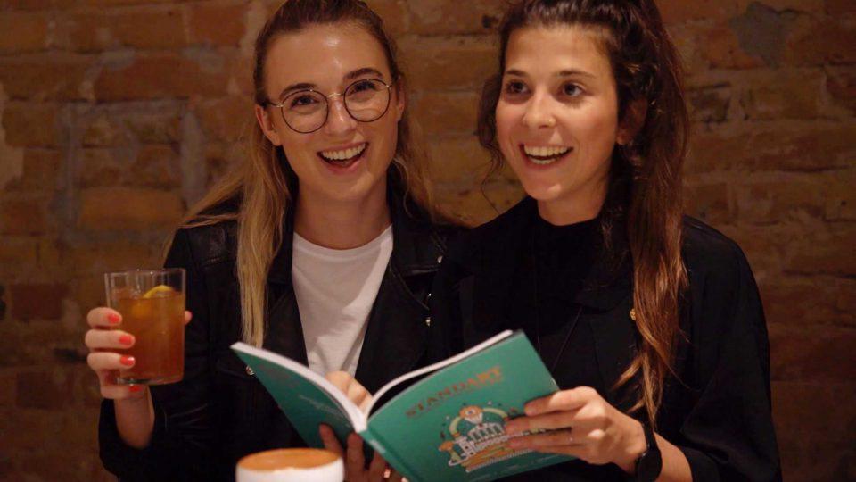 Zwei Gäste der Espresso Martini Party blättern durch das Standart Mag Magazin und lachen in die Kamera