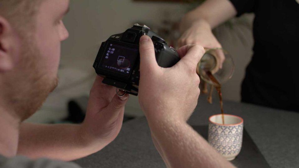 Dorian fotografiert mit einer Kamera wie Hanna Kaffee in eine Tasse schüttet als Verdeutlichung der Belichtungszeit