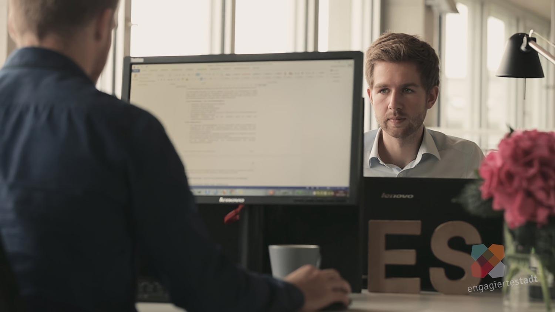 Zwei Mitarbeiter von Syspons im Büro arbeiten am Computer