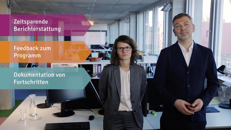Der Geschäftsführer Christoph Emminghaus und Hanna Hielscher von Syspons stehen im Büro. Neben ihnen sind 2d Motion Graphics