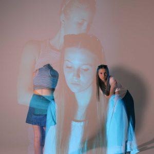 Laura und Malena posen für die Kamera mit blassem rosa und blauem Licht
