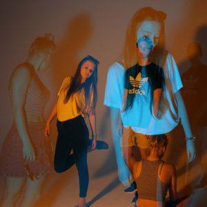 Laura, Adrian und Malena posen für die Kamera in blau und orangnem Licht