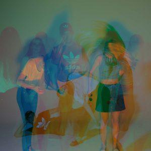 Laura, Adrian und Malena posen für die Kamera mit grün-blau und orange färbendem Licht