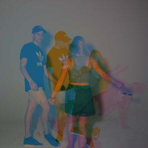 Laura, Adrian und Malena posen für die Kamera in Blau-Orange
