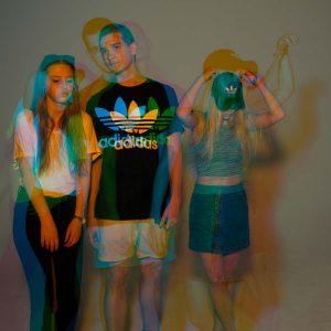 Laura, Adrian und Malena posen für die Kamera in Orange-Blauem Licht