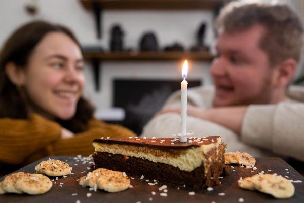 Hanna und Dorian feiern ihr Unternehmen mit einem stück Kuchen und einer Kerze.